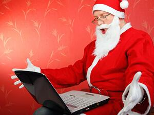 surprised santa claus get message on laptop computer. on the red background